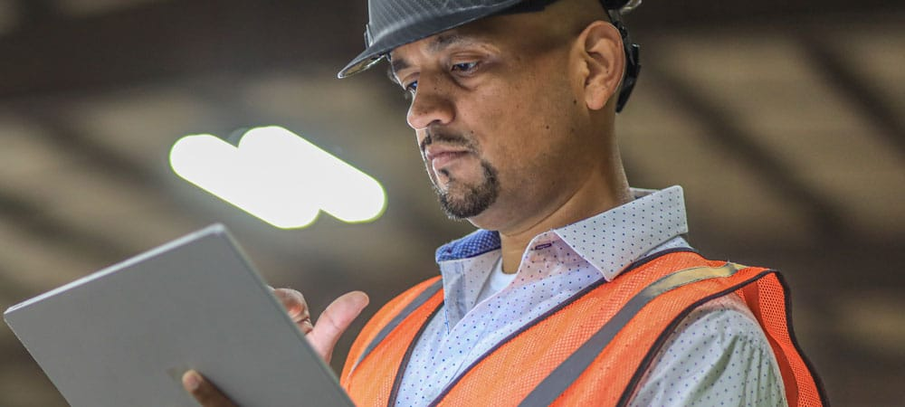 Kamps Employee looking at a tablet wearing safety vest and helmet